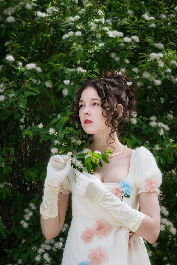 Mujer joven en un vestido blanco largo elegante de la novia en flores imagenes de archivo