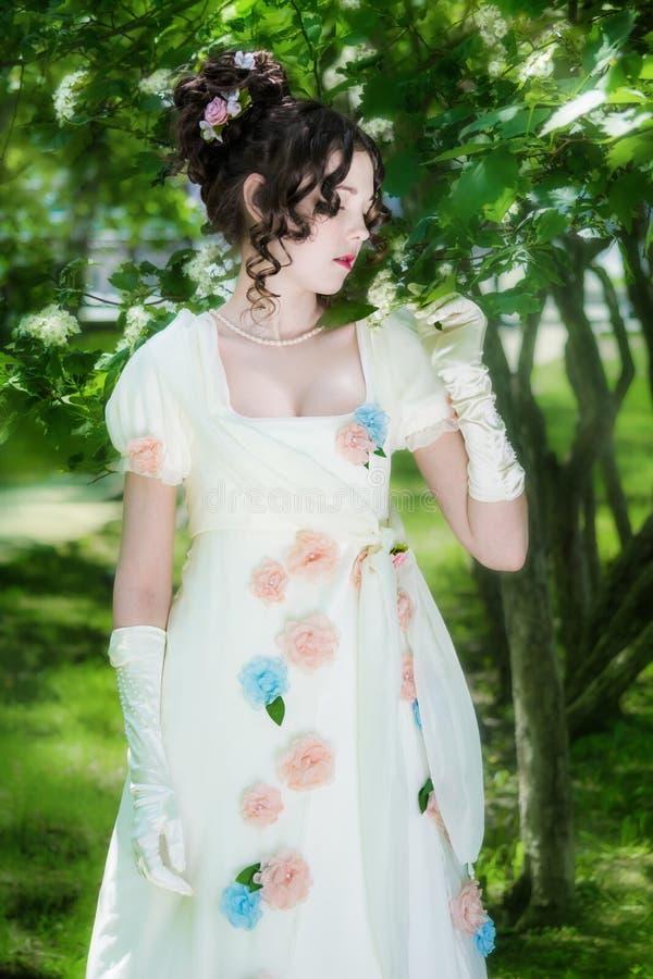 Mujer joven en un vestido blanco largo elegante de la novia en flores imágenes de archivo libres de regalías