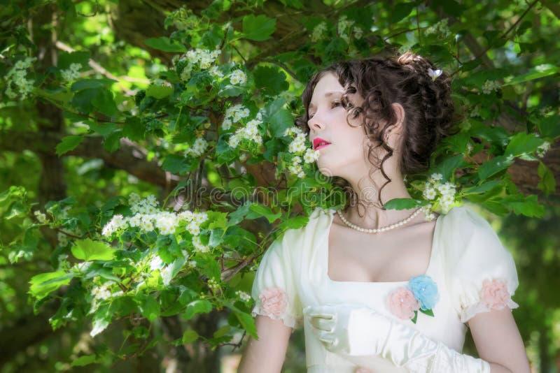Mujer joven en un vestido blanco largo elegante de la novia en flores imagen de archivo