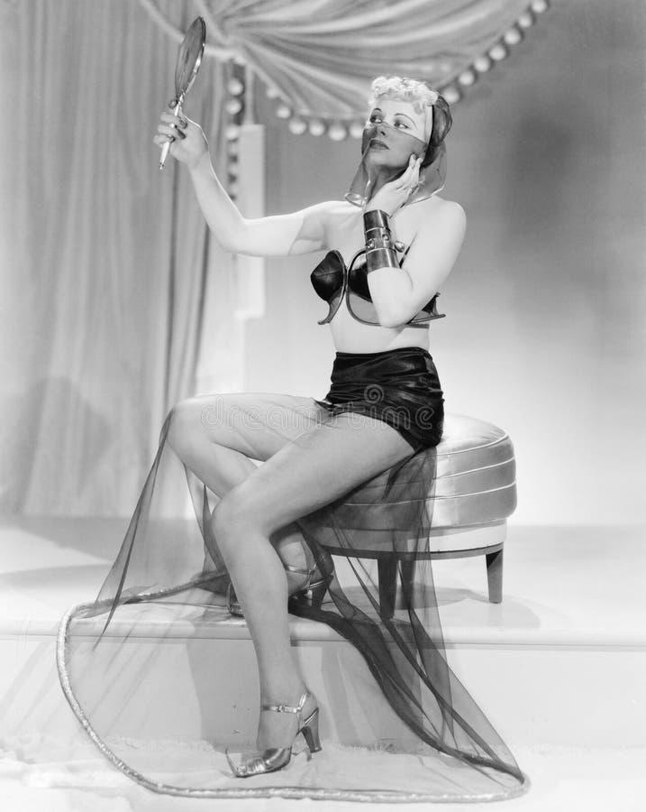 Mujer joven en un vestido inusual, sentándose en un taburete, mirando en un espejo (todas las personas representadas no son vivas fotografía de archivo libre de regalías