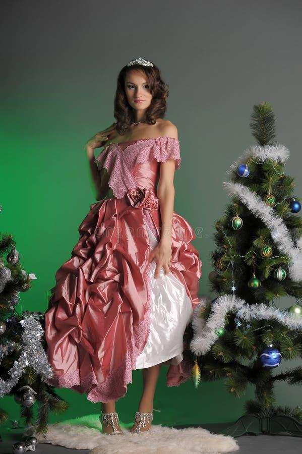 Mujer joven en un vestido rosado elegante con un árbol de navidad en a foto de archivo libre de regalías