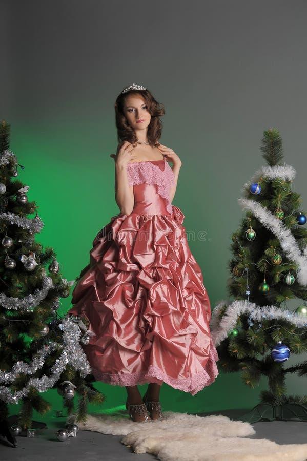 Mujer joven en un vestido rosado elegante con un árbol de navidad en a imagenes de archivo