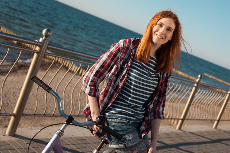 Mujer joven en una bicicleta imágenes de archivo libres de regalías