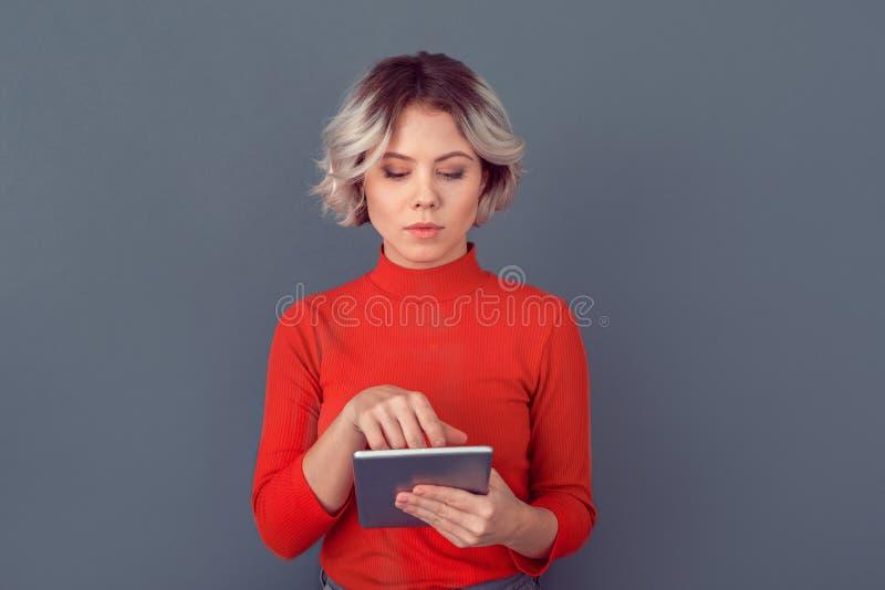 Mujer joven en una blusa roja aislada en la pared gris que trabaja en la tableta digital fotos de archivo