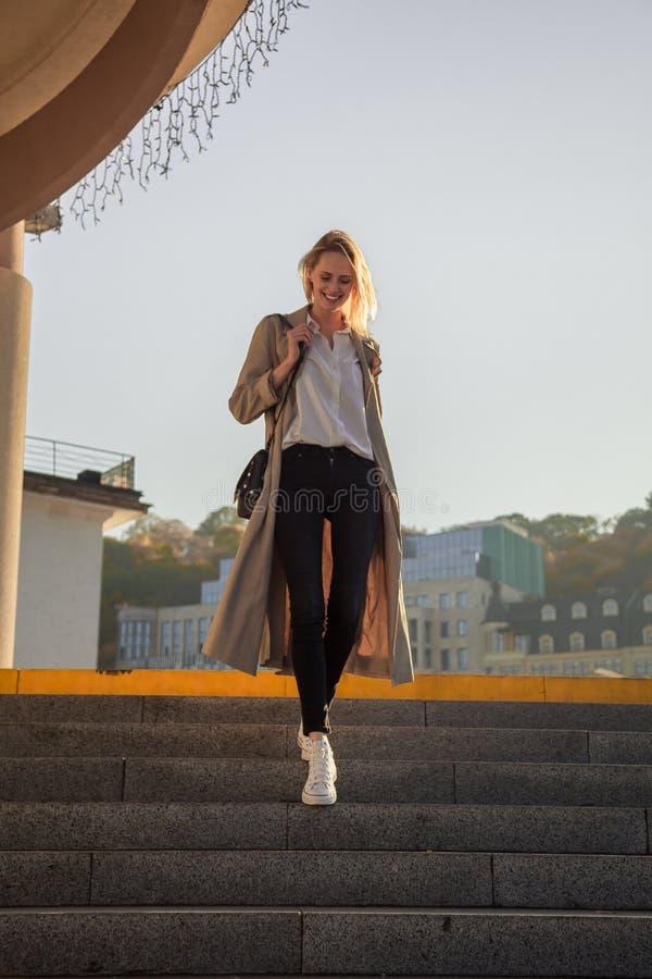 Mujer joven en una capa elegante de la primavera en vidrios de moda en una camiseta blanca en un bolso de cuero negro que camina  foto de archivo
