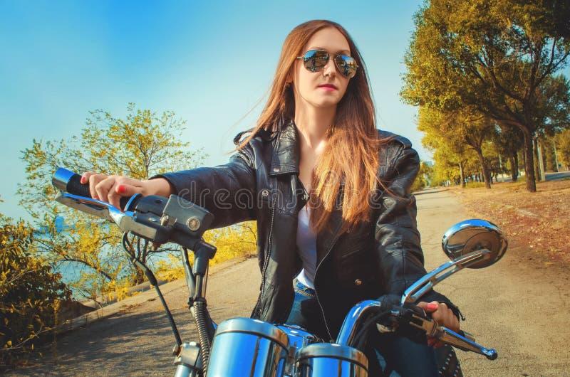 Mujer joven en una chaqueta de cuero y tejanos en vidrios encendido fotografía de archivo