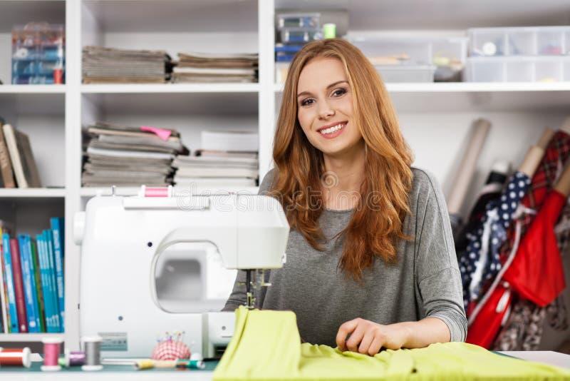 Mujer joven en una máquina de coser foto de archivo