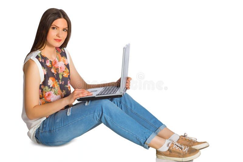 Mujer joven en vaqueros con el ordenador portátil que se sienta en piso fotografía de archivo libre de regalías