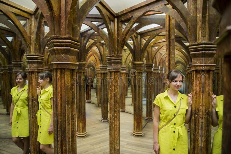 Mujer joven en vestido amarillo en sitio grande del espejo imagenes de archivo