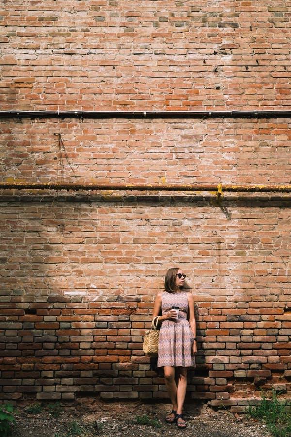 Mujer joven en vestido con el café a ir contra de brickwall imagen de archivo libre de regalías