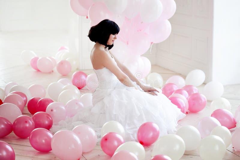 Mujer joven en vestido de boda en interior de lujo con una masa de globos rosados y blancos imagenes de archivo