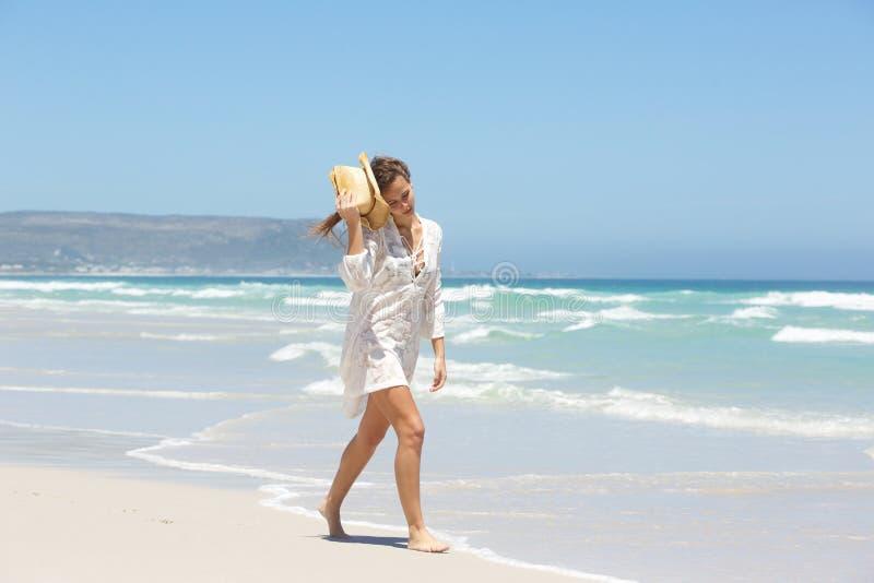 Mujer joven en vestido del verano que camina por la playa fotografía de archivo libre de regalías