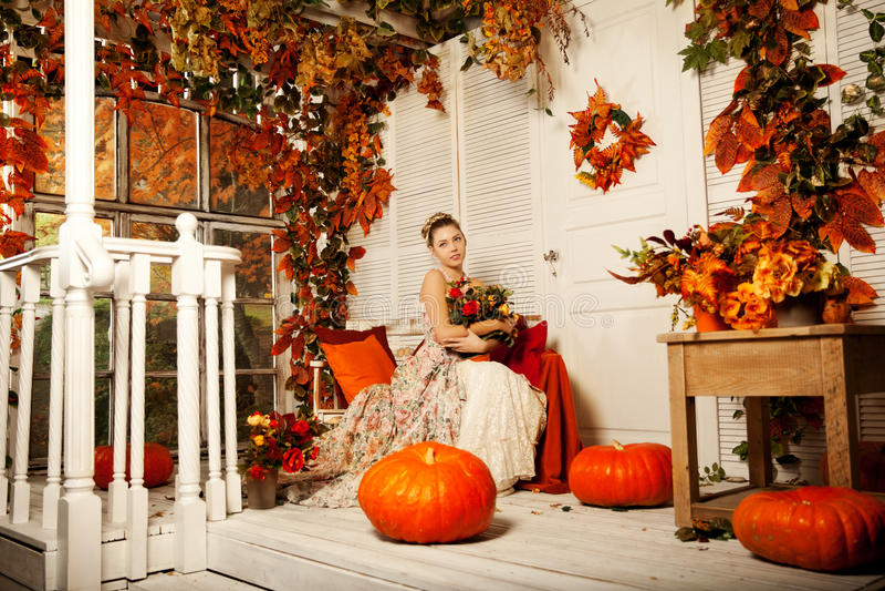Mujer joven en vestido del vintage en el pórtico del otoño Muchacha de la belleza en el fa imágenes de archivo libres de regalías