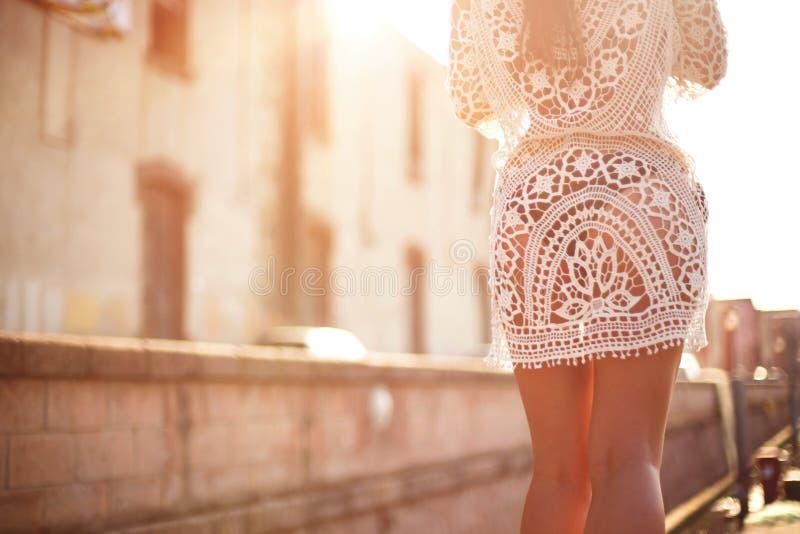 Mujer joven en vestido lindo del verano que camina en la puesta del sol foto de archivo