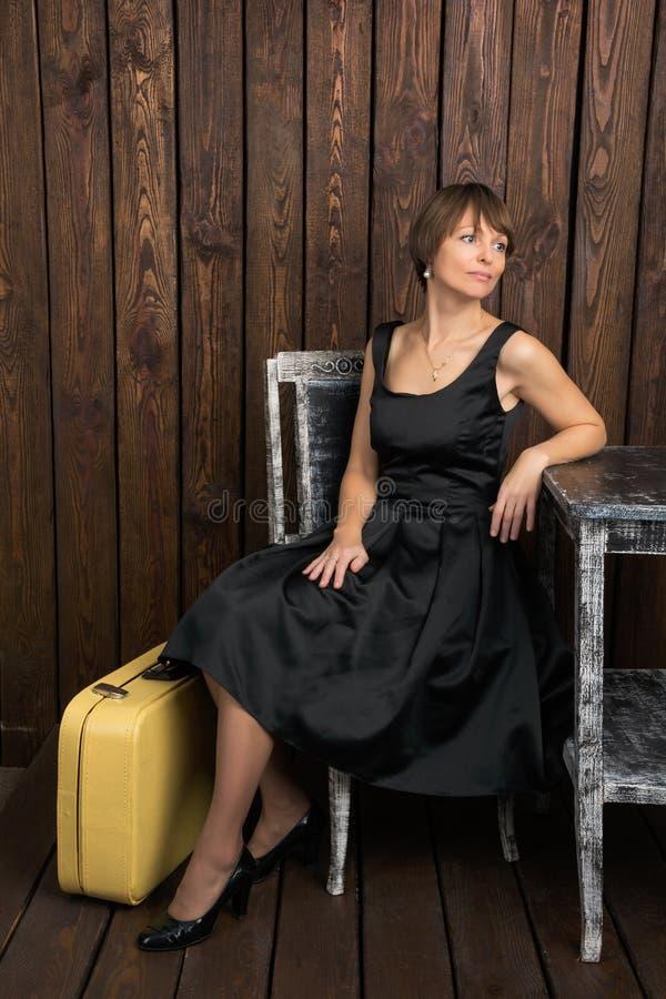 Mujer joven en vestido retro del negro del estilo con una maleta del vintage fotos de archivo libres de regalías