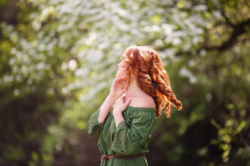 Mujer joven en vestido verde romántico en un jardín floreciente de la manzana imágenes de archivo libres de regalías