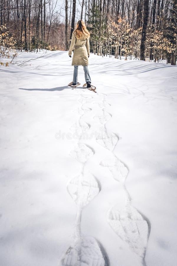 Mujer joven en zapatos de la nieve que camina en bosque del invierno imágenes de archivo libres de regalías