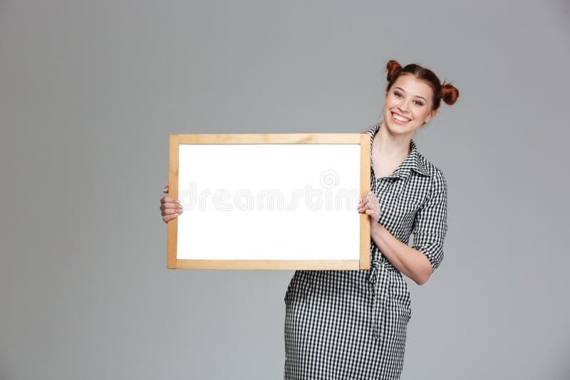 Mujer joven encantadora alegre que se coloca con whiteboard en blanco imágenes de archivo libres de regalías