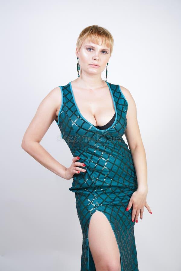 Mujer joven encantadora del tamaño extra grande con el pelo rubio corto vestido en un vestido largo lujoso del verde de la tarde  fotos de archivo