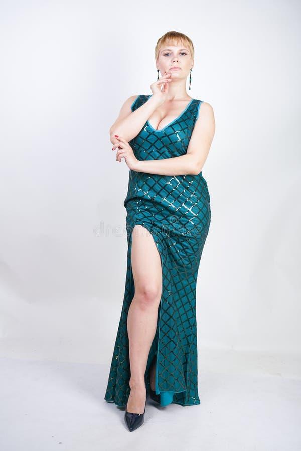 Mujer joven encantadora del tamaño extra grande con el pelo rubio corto vestido en un vestido largo lujoso del verde de la tarde  imágenes de archivo libres de regalías