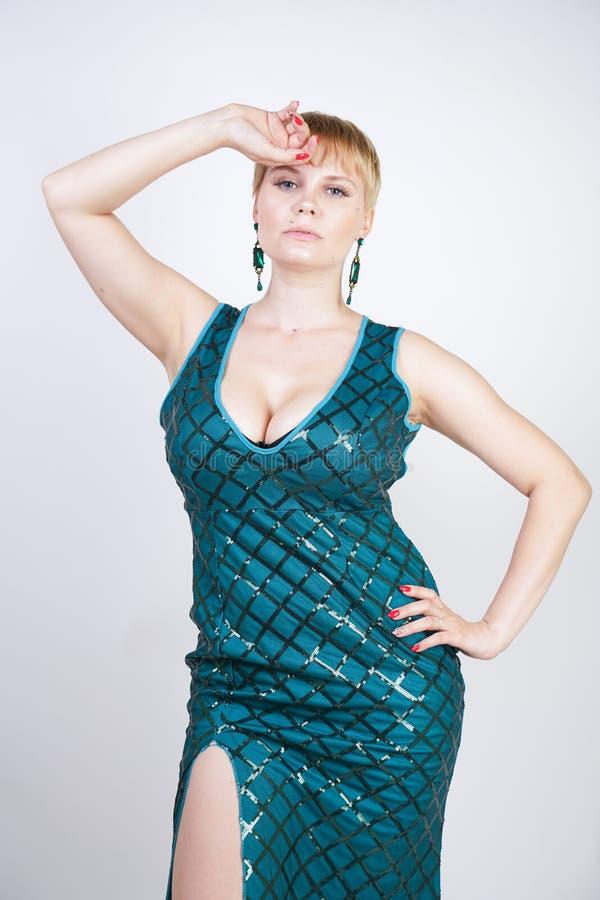 Mujer joven encantadora del tamaño extra grande con el pelo rubio corto vestido en un vestido largo lujoso del verde de la tarde  imagen de archivo libre de regalías