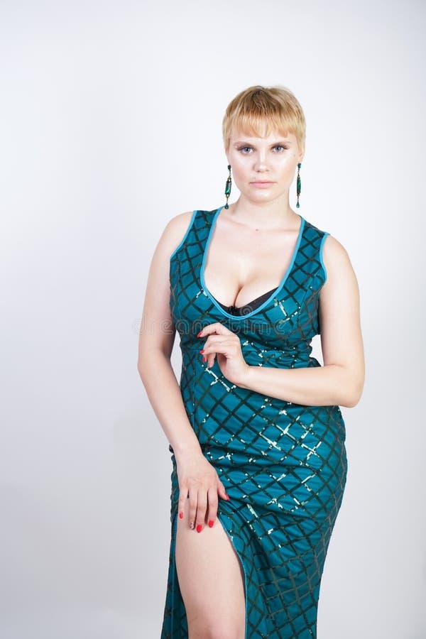 Mujer joven encantadora del tamaño extra grande con el pelo rubio corto vestido en un vestido largo lujoso del verde de la tarde  imagen de archivo