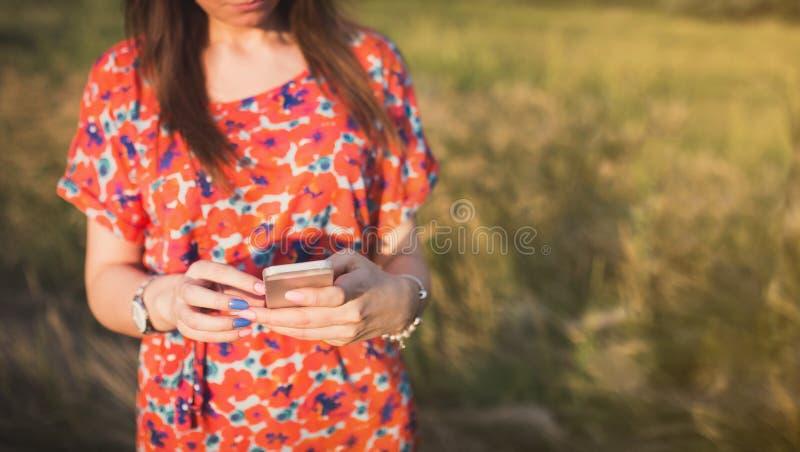 Mujer joven encantadora que usa al teléfono elegante móvil foto de archivo libre de regalías