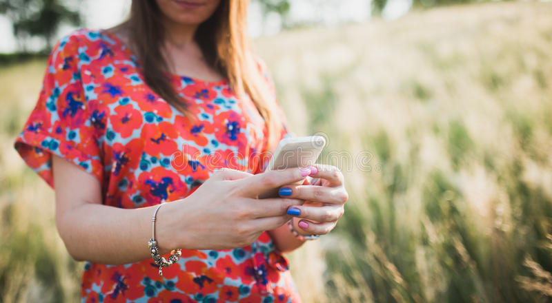 Mujer joven encantadora que usa al teléfono elegante móvil foto de archivo