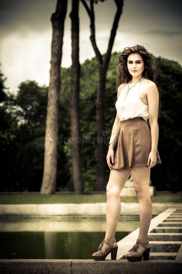 Mujer joven encantadora y hermosa con el pelo rizado al aire libre imagen de archivo