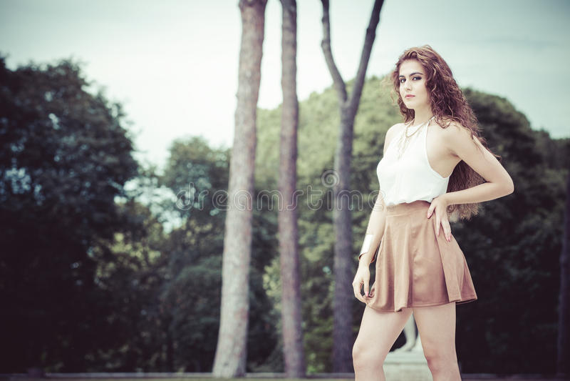 Mujer joven encantadora y hermosa con el pelo rizado al aire libre fotografía de archivo