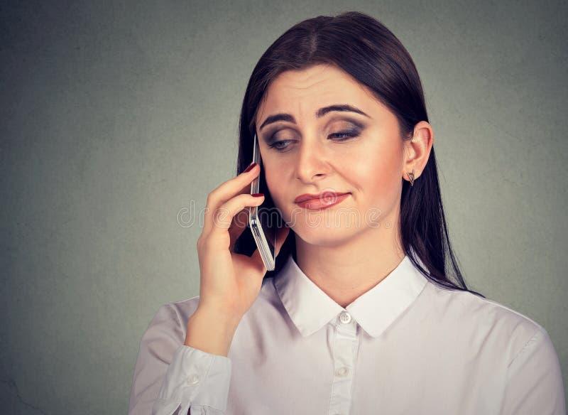 Mujer joven enfadada aburrida por la conversación telefónica larga foto de archivo libre de regalías