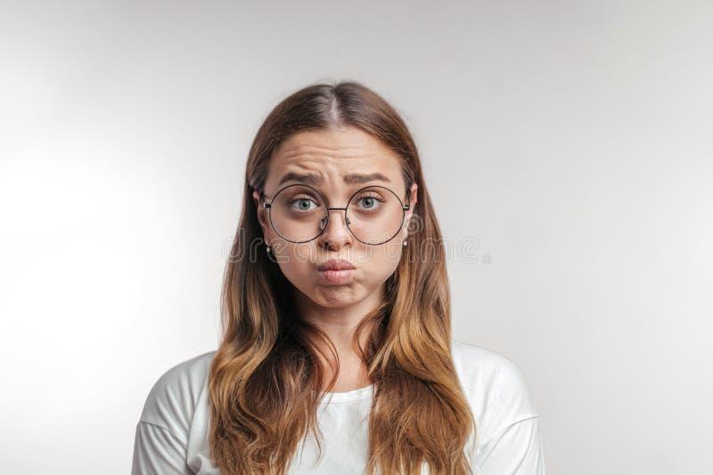Mujer joven enfadada, irritada que sopla sus mejillas, frunciendo el ceño, foto de archivo libre de regalías