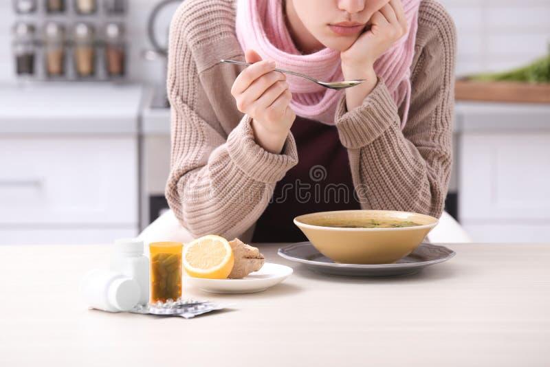 Mujer joven enferma que come el caldo para curar frío en la tabla imagenes de archivo