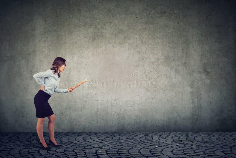 Mujer joven enojada con el rodillo que grita en alguien imagenes de archivo