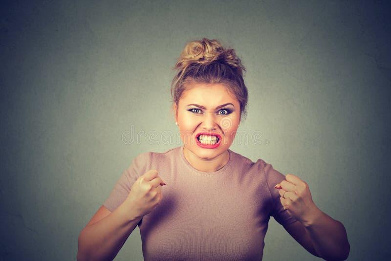 Mujer joven enojada con los puños para arriba que grita imagenes de archivo