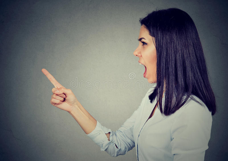 Mujer joven enojada del perfil lateral que grita imagen de archivo libre de regalías