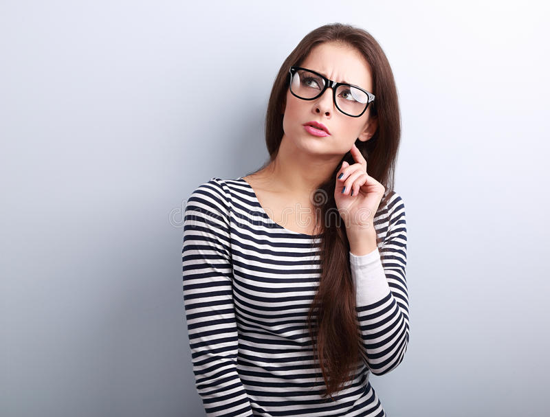 Mujer joven enojada enfadada en lentes que piensa y que mira para arriba fotografía de archivo libre de regalías