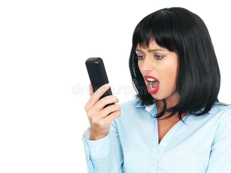 Mujer joven enojada frustrada que usa un teléfono celular o un teléfono de Chordless imagen de archivo