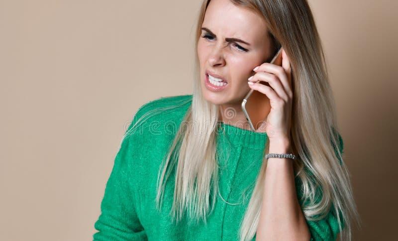 Mujer joven enojada que discute hablar en el teléfono imagen de archivo libre de regalías