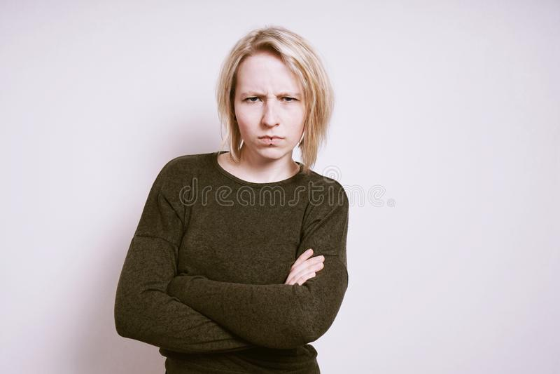 Mujer joven enojada que frunce el ceño con los brazos cruzados fotografía de archivo libre de regalías