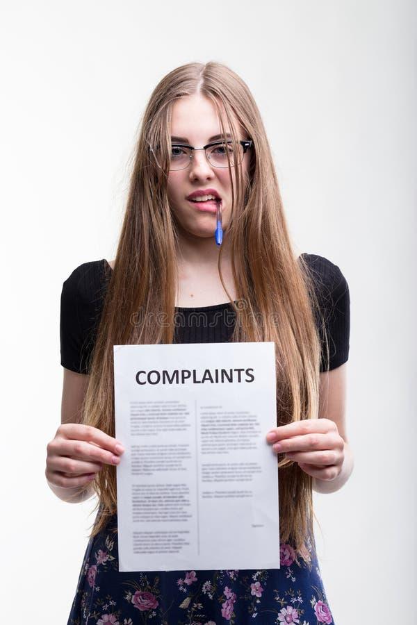 Mujer joven enojada que soporta una lista de denuncias imagen de archivo