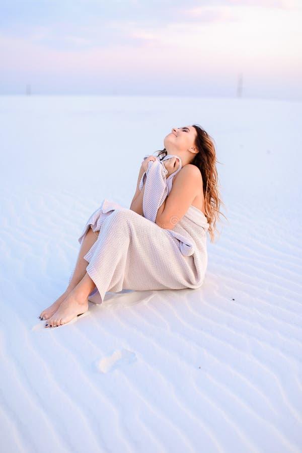 Mujer joven envuelta en la manta que se sienta en la arena blanca imagen de archivo