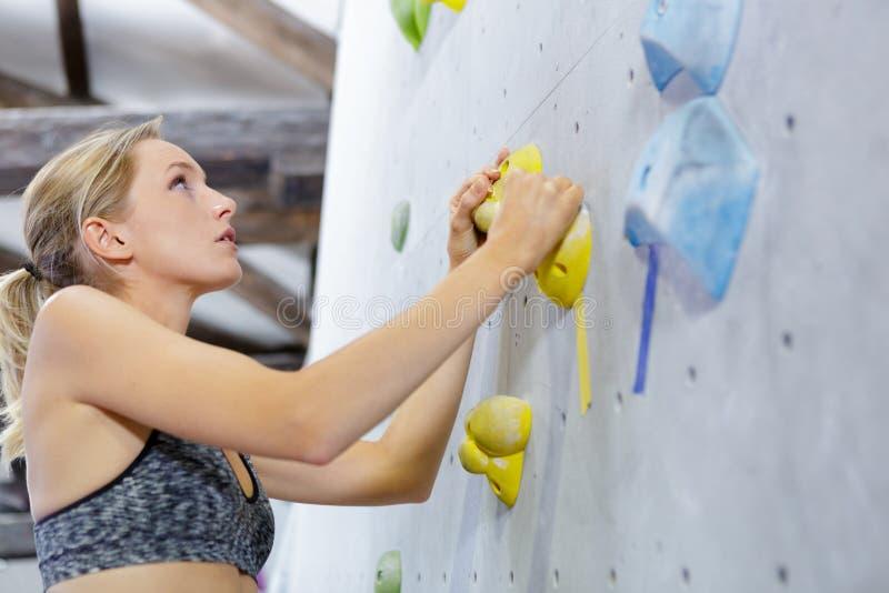 Mujer joven escaladora libre escalando roca artificial en interiores imagen de archivo libre de regalías
