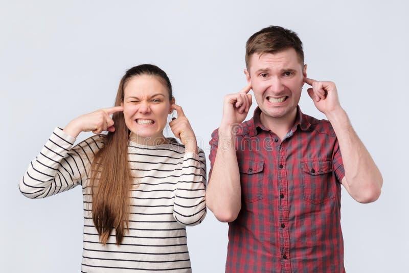Mujer joven europea de los pares de la familia y oídos de cierre del hombre debido a fuerte ruido desagradable foto de archivo libre de regalías