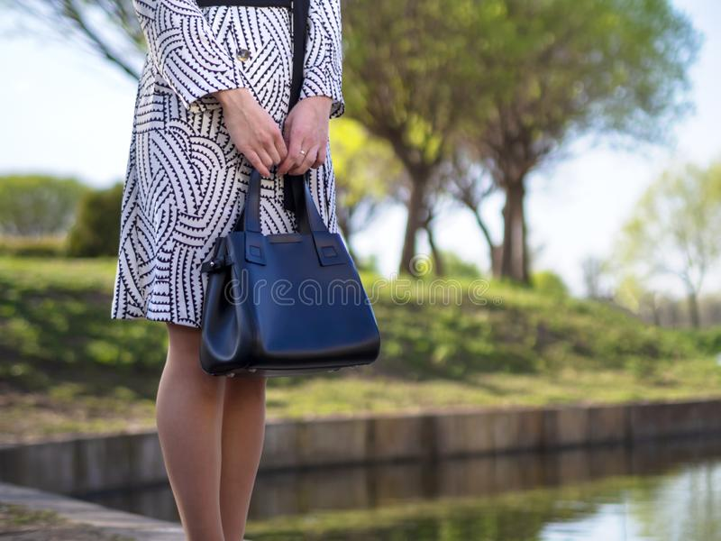 Mujer joven europea elegante en un impermeable, medias, zapatos con los talones, con un bolso de cuero negro en sus manos en un p imagen de archivo libre de regalías
