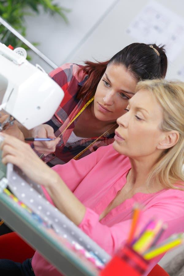 Mujer joven experimentada de la alcantarilla enseñando a cómo coser foto de archivo libre de regalías