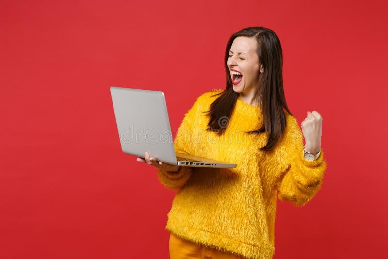 Mujer joven extática en suéter amarillo de la piel con los ojos cerrados griterío, sosteniendo el ordenador de la PC del ordenado foto de archivo