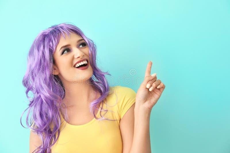 Mujer joven extravagante con el dedo índice aumentado en fondo del color fotografía de archivo libre de regalías
