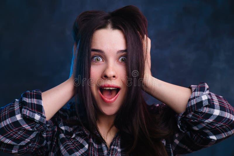 Mujer joven extremadamente sorprendida, emocionada, chocada que toca su h fotos de archivo