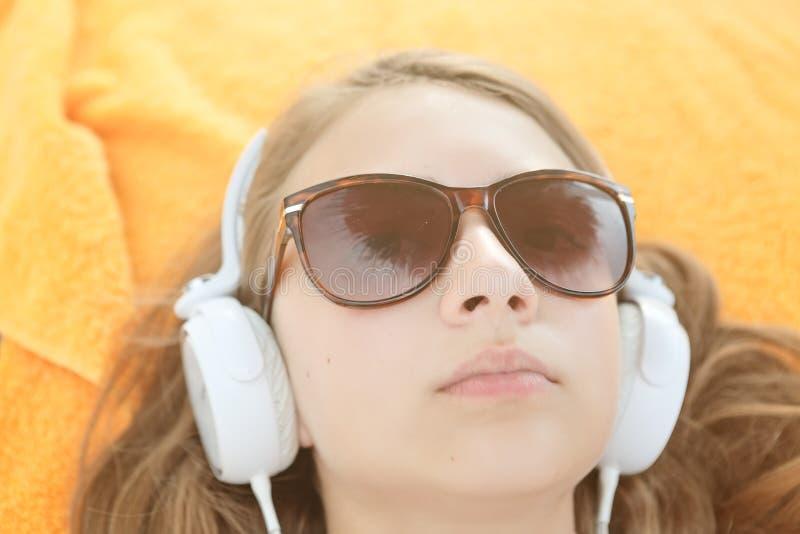 Mujer joven fascinante que disfruta de música preferida en auriculares blancos grandes Foto interior del primer de la canción que foto de archivo libre de regalías